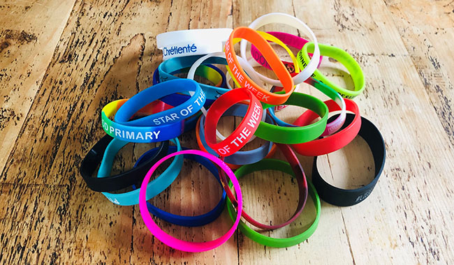 A variety of brightyly coloured personalised wrist bands
